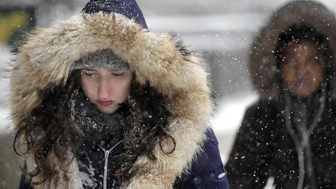 Bundled against the cold, wet conditions, University of Wisconsin-Madison student Natalie Weill makes her way through the campus' Library Mall as a steady snowstorm moves throughout the Madison, Wis. area Tuesday, March 5, 2013. (AP Photo/Wisconsin State Journal, John Hart)