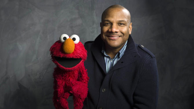 """FILE - In this Jan. 24, 2011 file photo, Elmo puppeteer Kevin Clash poses with the """"Sesame Street"""" muppet in the Fender Music Lodge during the 2011 Sundance Film Festival in Park City, Utah. (AP Photo/Victoria Will, File)"""