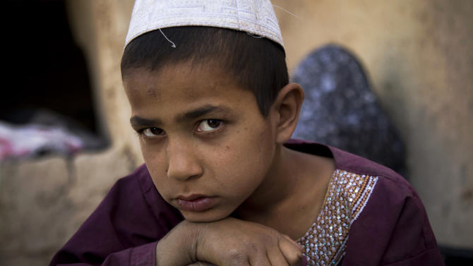"""This Saturday, April 20, 2013 photo shows 8-year-old son, Hikmatullah, in Kandahar, Afghanistan. He said he remembers the sight of the attacker in full military uniform. """"I was so afraid. I pretended I was asleep."""" His mother, Masooma, said the soldier found him and punched him repeatedly in the head. (AP Photo/Anja Niedringhaus)"""