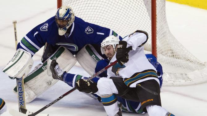 San Jose Sharks center Benn Ferriero, right front, ties to get a shot past Vancouver Canucks goalie Roberto Luongo (1) and defenseman Keith Ballard (4) during the third period of an NHL hockey game in Vancouver, British Columbia, Monday, Jan. 2, 2012. (AP Photo/The Canadian Press, Jonathan Hayward)