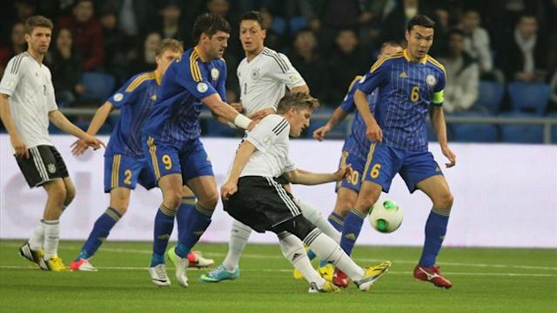 Kazakhstan players Sergei Ostapenko (front L No.9) and Kairat Nurdauletov (front R No.6) vie with Germany's Bastian Schweinsteiger (C) during their 2014 World Cup qualifying football match in the Kazakh capital Astana (AFP)