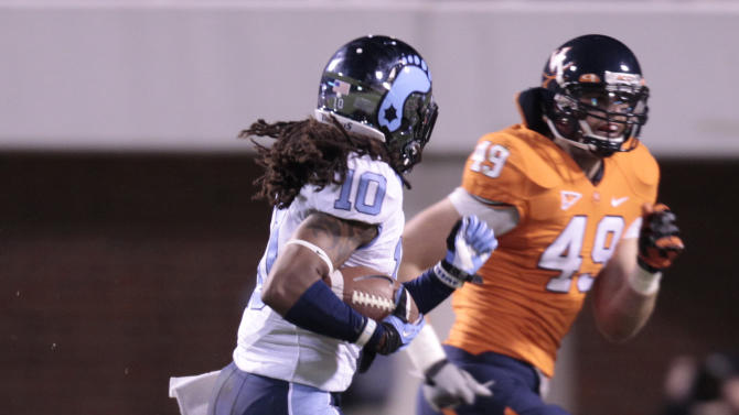North Carolina safety Tre Boston (10) returns an interception for a touchdown Virginia fullback Zachary Swanson (49) closes in during the first half of an NCAA college football game at Scott stadium  Thursday, Nov. 15, 2012 in Charlottesville, VA.  (AP Photo/Steve Helber)
