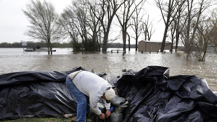 Bob Bailey tinkers with a pump as he tries to keep floodwater from the Mississippi River out of one of his rental properties Sunday, April 21, 2013, in Clarksville, Mo. Many have come to the aid of the tiny community, working since Wednesday to build a makeshift sandbag levee that seemed to be holding as the crest, expected to be 11 feet above flood stage, approaches. (AP Photo/Jeff Roberson)