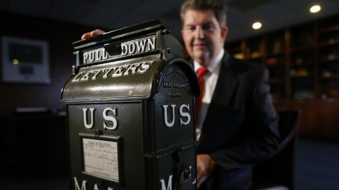Postmaster General Patrick R. Donahoe poses with a mailbox from the early 1900's during an interview with the Associated Press at his office at U.S. Postal Service Headquarters in Washington, Thursday, Aug. 1, 2013. Donahoe has a wish list for raising cash for his financially ailing agency. High on it is delivery of beer, wine and spirits. In an interview with The Associated Press, Donahoe also endorsed ending most door-to-door and Saturday mail deliveries as cost-saving measures. (AP Photo/Charles Dharapak)