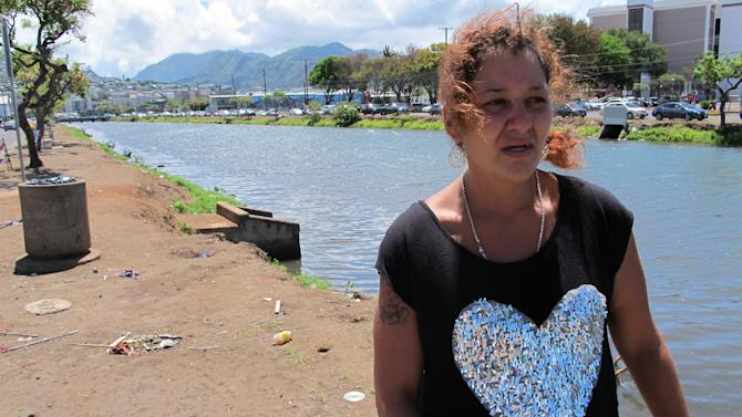 Stefanie Sanchez talks about what it's like to live along the banks of a canal on Tuesday, June 9, 2015 in Honolulu. Sanchez has lived in a tent there for several months, and the city of Honolulu sent a crew to clean up the area on Tuesday. (AP Photo/Cathy Bussewitz)