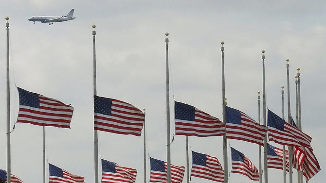 A jetliner flies over flags flying at half-staff at the Washington Monument in Washington, Tuesday, April 16, 2013, after President Obama ordered flags to be lowered on federal building to honor the loss of life from the explosions at the Boston Marathon. (AP Photo/J. David Ake)