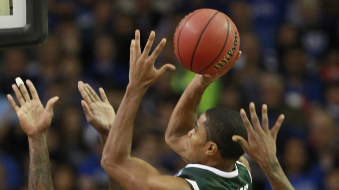 Michigan State guard Gary Harris (14) shoots over the defense of Kansas forward Jamari Traylor (31) and guard Ben McLemore (23) during the first half of an NCAA college basketball game at the Georgia Dome in Atlanta Tuesday, Nov. 13, 2012. (AP Photo/John Bazemore)