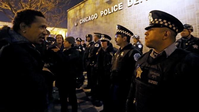A demonstrator faces a line of police in front of the Chicago Police Department during protests in Chicago