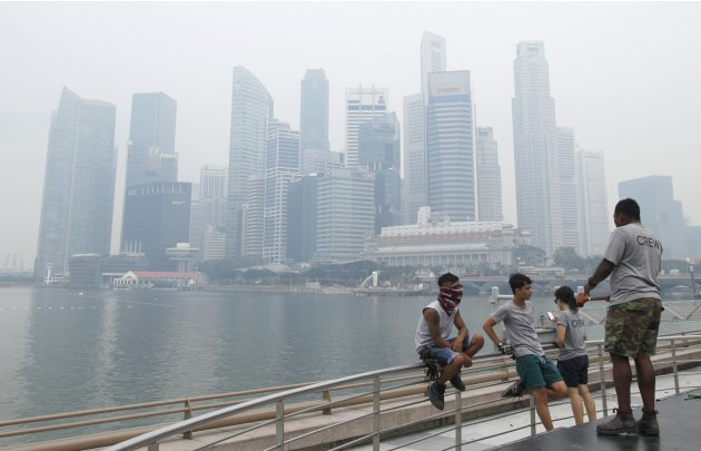 Workers take a break in front of the hazy skyline of Singapore