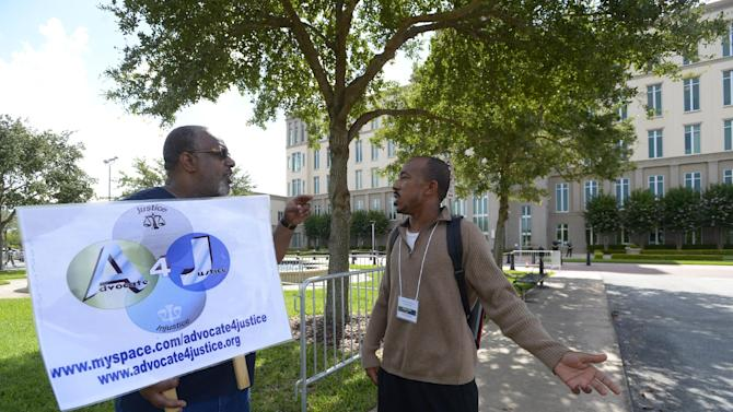 Garry Jones, left, of Atlanta, Ga., and H. Alexander Duncan, of Eatonville, Fla., an attendee of the George Zimmerman trial, discuss the trial outside the Seminole County Courthouse in Sanford, Fla., Thursday, June 20, 2013. Zimmerman has been charged with second-degree murder for the 2012 shooting death of Trayvon Martin.(AP Photo/Phelan M. Ebenhack)