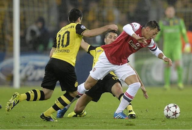 Dortmund's Henrikh Mkhitaryan, left, and Arsenal's Mesut Ozil challenge for the ball during the Champions League group F soccer match between Borussia Dortmund and Arsenal FC in Dortmund, Germany, Wed