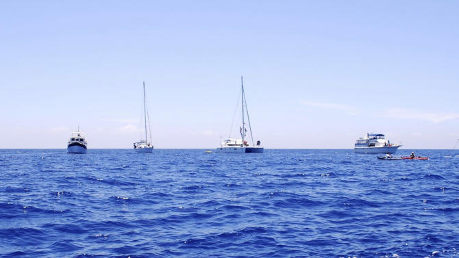 In this photo provided by Diana Nyad via the Florida Keys News Bureau, boats escorting endurance swimmer Diana Nyad ply the Florida Straits between Cuba and the Florida Keys Monday, Aug. 20, 2012. After being delayed by a weather squall line late Sunday night and early Monday morning, her team reported that Nyad was back on course in her effort to be the first swimmer to transit the Florida Straits from Cuba to the Keys without a shark cage. (AP Photo/Diana Nyad via the Florida Keys News Bureau, Christi Barli)