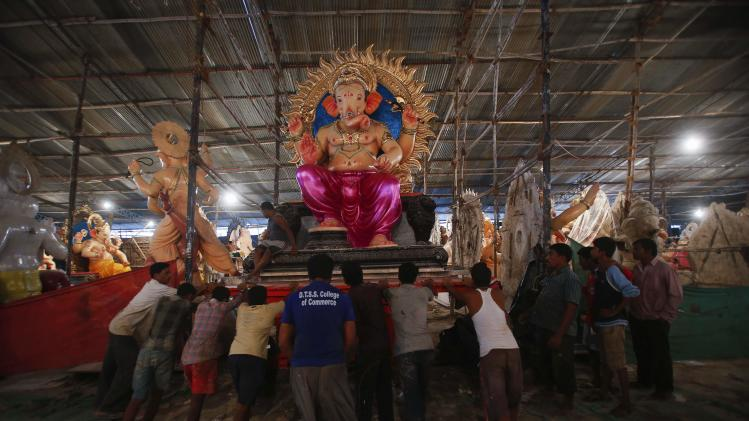 Workers push a trolley with an idol of Hindu elephant god Ganesh, the deity of prosperity, as it is transported from a workshop to a place of worship in Mumbai