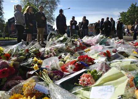 People view flowers left outside an army barracks near the scene of a killing in Woolwich