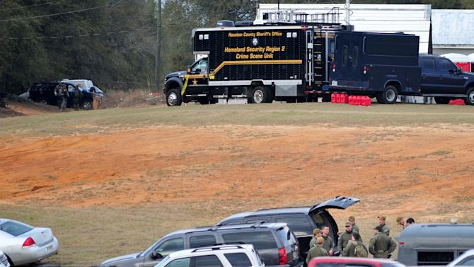 Federal and local law enforcement officers gather at their trucks after the hostage crisis ended in Midland City, Ala., on Monday afternoon, Feb. 4, 2013.  Officials say they stormed a bunker in Alabama to rescue a 5-year-old child being held hostage there after his abductor was seen with a gun. (AP Photo/The Dothan Eagle, Jay Hare)