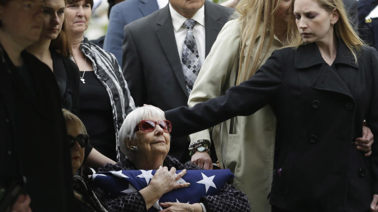 Shirley Woodward, mother of Cynthia McLelland holds a flag and is comforted by family after memorial services for her daughter and son-in-law Kaufman County District Attorney Mike McLelland after a memorial services in Mesquite, Texas, Thursday, April 4, 2013.  The Kaufman County District Attorney Mike McLelland and his wife, Cynthia, were found shot to death Saturday in their house near Forney, about 20 miles east of Dallas. No arrests have been made. (AP Photo/LM Otero)
