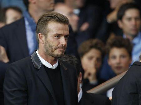 Former soccer player Beckham arrive to attend the Champions League Group F soccer match between Paris St Germain and Barcelona at the Parc des Princes Stadium in Paris