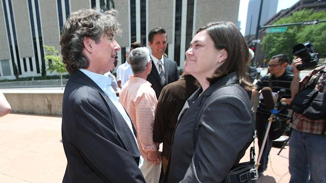 Two plaintiffs in a lawsuit to overturn Colordo's gay marriage ban, Cassie Rubald, left, and her partner, Rachel Catt, hold hands during a news conference outside the federal courthouse in downtown Denver on Tuesday, July 1, 2014. Six gay couples filed the lawsuit to ask for an injunction to stop all officials from enforcing the ban on gay marriage in Colorado. (AP Photo/David Zalubowski)
