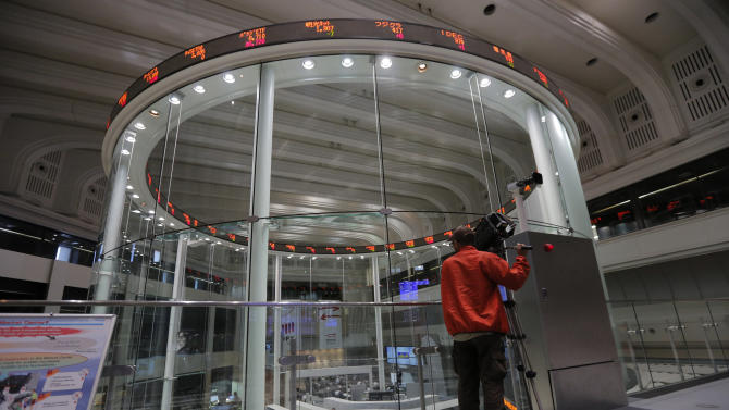 A TV cameraman films at the Tokyo Stock Exchange in Tokyo, Wednesday, May 22, 2013.  Asian stock markets were mostly higher Wednesday after investor confidence was boosted by a Federal Reserve official's comments that the U.S. central bank should stick with its super-easy monetary policy. (AP Photo/Itsuo Inouye)