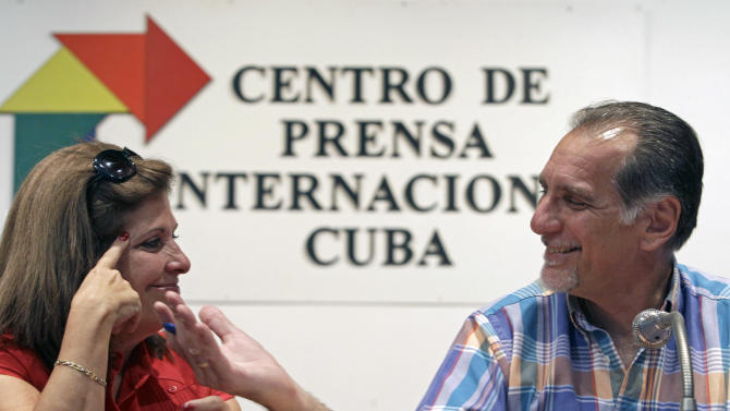 """Cuban agent Rene Gonzalez, 56, smiles at his wife Olga Salanueva during a press conference in Havana, Cuba, Friday, May 10, 2013. Gonzalez who spent 13 years in a U.S. prison renounced his American citizenship Monday, May 6, 2013, as part of a deal that allows him to avoid returning to the United States to serve out the remainder of his probation. Gonzalez, is one of the so-called """"Cuban Five"""" intelligence agents convicted in 2001 of spying on U.S. military installations in South Florida, exile groups and politicians. (AP Photo/Franklin Reyes)"""