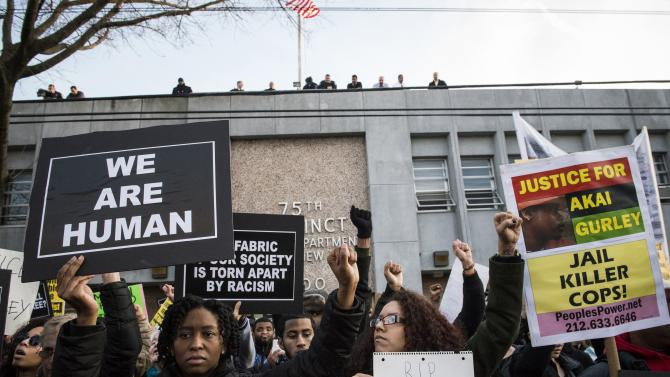Protesters, demanding justice for Akai Gurley, turn their backs towards the New York Police Department's (NYPD) 75th Precinct after marching their from the site of his shooting death in Brooklyn, New York