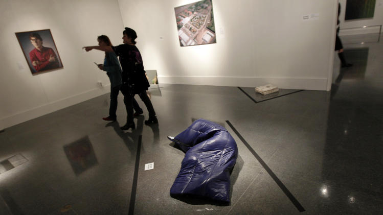 "In this Wednesday, Nov. 14, 2012 photo, museum patrons walk past a painted bronze sleeping bag, titled ""Nomad,"" by artist Gavin Turk, at the New Orleans Museum of Art in New Orleans. The piece is part of ""Lifelike,"" a traveling exhibit at the New Orleans Museum of Art through Jan. 27. (AP Photo/Gerald Herbert)"