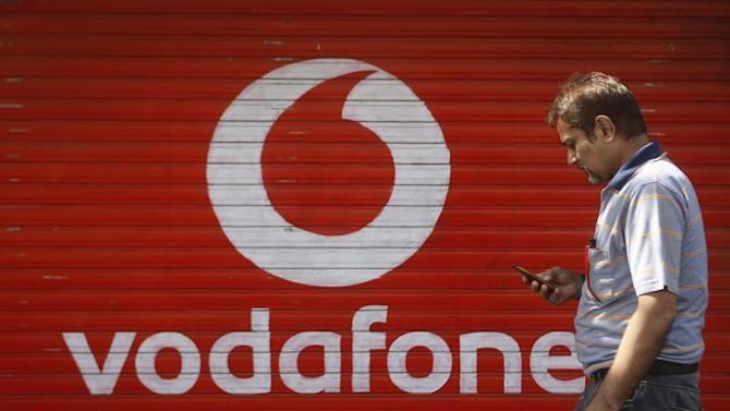 A man checks his mobile phone as he walks past a shop displaying the Vodafone logo on its shutter in Mumbai
