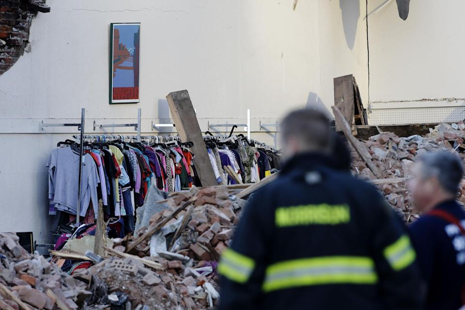 Firefighters view the aftermath of a building collapse, Thursday, June 6, 2013, in Philadelphia. Wednesday a building under demolition collapsed onto a neighboring thrift store, killing six people and injuring 14, including one who was pulled from the debris nearly 13 hours later. (AP Photo/Matt Rourke)