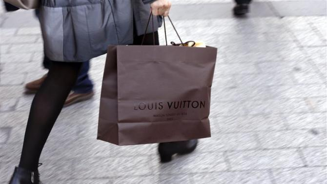A woman walks with a Louis Vuitton shopping bag as she leaves a Louis Vuitton store in Paris