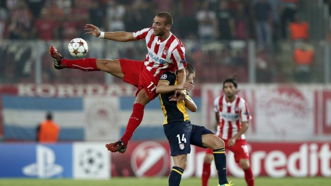 Olympiakos' Kasami jumps for the ball against Atletico Madrid's Gabi during their Champions League soccer match at Karaiskaki stadium in Piraeus near Athens