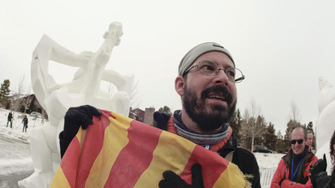 IMAGE DISTRIBUTED FOR BRECKENRIDGE RESORT CHAMBER- Team Catalonia, Spain captain, Lluis Ribalta Coma-Cros holds his motherland flag after finishing his masterpiece 'Banyista Nua (Homage To Picasso) snow sculpture that started out of a 12 foot tall, 20-ton block of compacted snow at the outdoor art gallery during the 23 annual International Snow Sculpture Championships in Breckenridge, Colo., on Saturday, Jan. 26, 2013. A total of 15 international teams participated in this invited competition. The sculptures will remain on display through Feb. 3, 2013, weather permitting. Visit www.gobreck.com for more information. (Nathan Bilow/AP Images for the Breckenridge Resort Chamber)