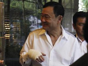 Thailand's former prime minister Thaksin Shinawatra sports a bandaged hand as he leaves a meeting at a hotel in Singapore