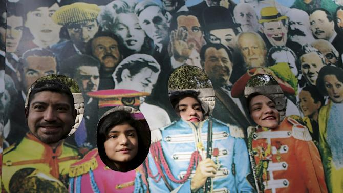 People pose with a photo of the British band The Beatles during an attempt to set a Guinness World Record for the largest number of people dressed as members of the band at a park in Mexico City