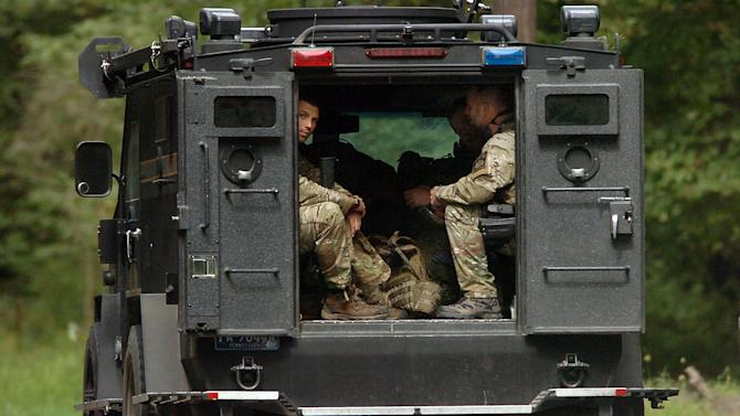 Members of the Pennsylvania State Trooper's Tactical Response Unit, ride along Route 447 in Barrett Township on Saturday, Sept. 20, 2014, near Canadensis, Pa., during a search for suspected killer Eric Frein. Frein is suspected of fatally shooting a state trooper and wounding another at the Blooming Grove state police barracks a week earlier. (AP Photo/Scranton Times & Tribune, Butch Comegys)