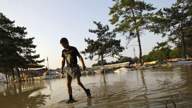 A man walks along a flooded playground at the city stadium in Krimsk, about 1,200 kilometers (750 miles) south of Moscow, Sunday, July 8, 2012. Intense flooding in the Black Sea region of southern Russia killed at least 150 people after torrential rains dropped nearly a foot of water, forcing many to scramble out of their beds for refuge in trees and on roofs, officials said Saturday. (AP Photo/Sergey Ponomarev)