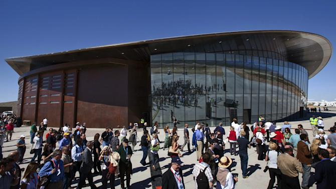 FILE - In this Oct. 17, 2011 file photo, guests stand outside the new Spaceport America hangar in Upham, N.M. Virgin Galactic has agreed to start paying New Mexico rent on the nearly quarter-billion dollar spaceport the state built for British businessman Richard Branson's space tourism business, but it says it is doing so under protest and without waiving its right to walk away from the project, according to documents obtained by The Associated Press.(AP Photo/Matt York, File)
