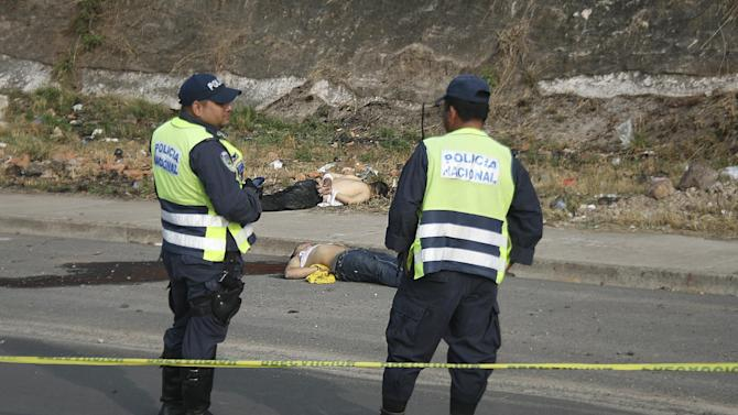 """In this March 23, 2013 photo, police stand next to the bodies of Billy """"Babyface"""" Jovel Mejia, 23, and Wilder Javier """"Sadboy"""" Alvarado, 20, after they were found dead on the outskirts of the Tegucigalpa, Honduras. Each had a single 9 millimeter gunshot to the head, and their hands were tightly bound. Jovel was missing his right eye, Alvarado his left. Alvarado's mother, Norma, said police had raided her home at least six times in search of her son. (AP Photo/Fernando Antonio)"""
