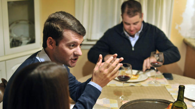 In this photo taken Friday, Nov. 16, 2012, Brian Malone, of Duxbury Mass., speaks about the recent presidential election, while gathered with his extended family including his wife Rebecca Malone, left, and brother-in-law Andrew Marshall, right, of Quincy Mass., during dinner at his in-law's house in Hingham, Mass., where politics is a frequent, and divisive topic of conversation. (AP Photo/Josh Reynolds)