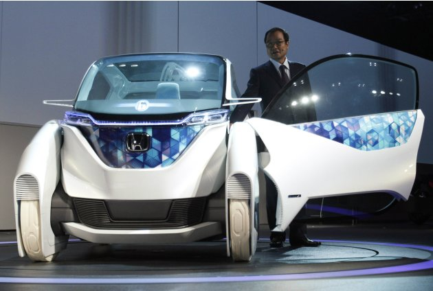 Honda Motor Co President Ito speaks next to the company's electric Micro Commuter Concept city in Tokyo