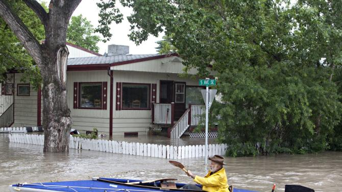 A kayaker paddles down a flooded street in High River, Alberta on Thursday, June 20, 2013 after the Highwood River overflowed its banks. Calgary city officials say as many as 100,000 people could be forced from their homes due to heavy flooding in western Canada, while mudslides have forced the closure of the Trans-Canada Highway around the mountain resort towns of Banff and Canmore. (AP Photo/The Canadian Press, Jordan Verlage)