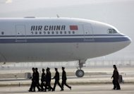 Airport security officials walk past an Air China plane queing to take off at the Beijing Capital International airport in 2006. Animal rights group PETA urged its supporters Thursday to bombard Air China with emails urging it to stop transporting monkeys from Asia to laboratories in the United States