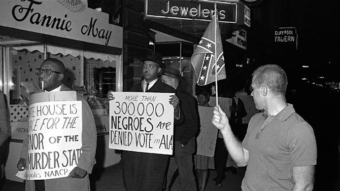 "FILE - In this April 14, 1964 black-and-white file photo, a man holds a Confederate flag at right, as demonstrators, including one carrying a sign saying: ""More than 300,000 Negroes are Denied Vote in Ala"", demonstrate in front of an Indianapolis hotel where then-Alabama Governor George Wallace was staying. After more than a century, the Census Bureau is dropping use of the word ""Negro"" to describe black Americans in its surveys. Instead of the term popularized during the Jim Crow era of racial segregation, census forms will use the more modern-day labels, ""black"" or ""African-American"".  (AP Photo/Bob Daugherty, File)"