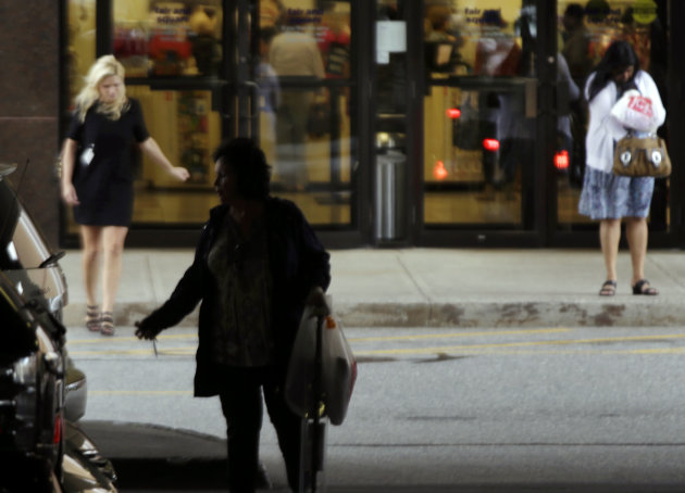 In this Monday, Sept. 10, 2012, photo, shoppers leave a store in Salem, N.H. Americans may have slowed their spending in September after splurging in the month before during the busy back-to-school shopping season. But most importantly, they are still spending. Still, given the economic and political uncertainty that weighs on many Americans right now, analysts say the results are an encouraging sign for stores as they head into what's traditionally the busiest shopping period of the year in November and December. (AP Photo/Elise Amendola)