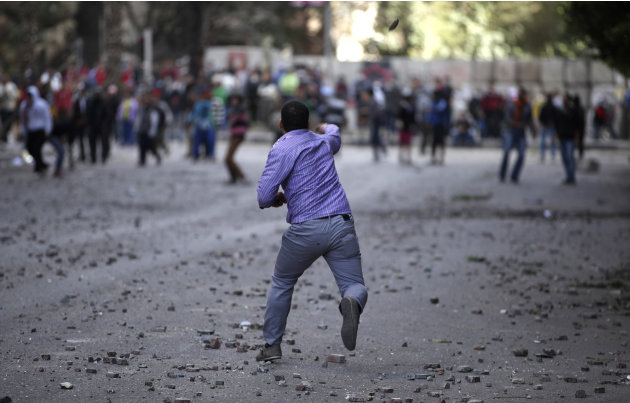 Pro and anti-government protesters throw stones during clashes near Tahrir Square in Cairo, Egypt, Wednesday, Jan. 30, 2013. Egypt's liberal opposition leader called for a broad national dialogue with
