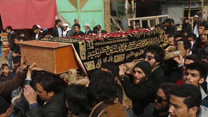 Afghans carry the coffin of Afghan cameraman Hatami, who died on Saturday of injuries sustained in a Taliban attack at a French cultural centre, in Kabul