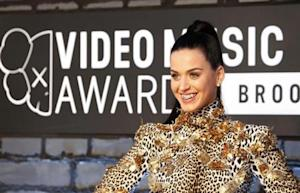 Singer Katy Perry shows off her bejeweled teeth on arrival for the 2013 MTV Video Music Awards in New York
