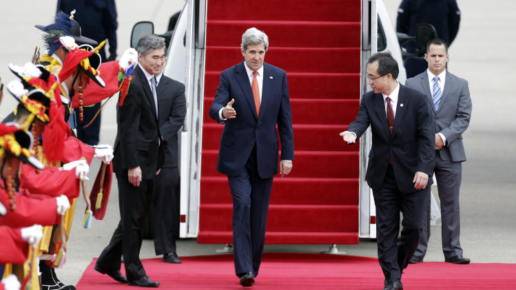 U.S. Secretary of State John Kerry, center, is escorted by South Korea's Foreign Ministry North American Affairs Bureau, Deputy Director General Moon Seoung-hyun, right, as Ambassador to South Korea Sung Kim, left, follows upon his arrival at Seoul military airport in Seongnam, South Korea, Friday, April 12, 2013. Kerry is traveling to Asia to meet with U.S. allies and visit here on the first leg of his three-nation Asian tour. (AP Photo/Lee Jin-man)