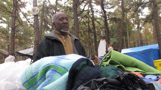 """In this Oct. 24, 2012 photo, Gregory """"Pops"""" Maple, one of three representatives chosen by members of a homeless encampment in Lakewood N.J. to represent their interests during an election in October, sorts through donated clothing at the camp.The camp was declared officially closed on June 30, 2014 when the last of its 120 occupants was given temporary housing.(AP Photo/Wayne Parry)"""