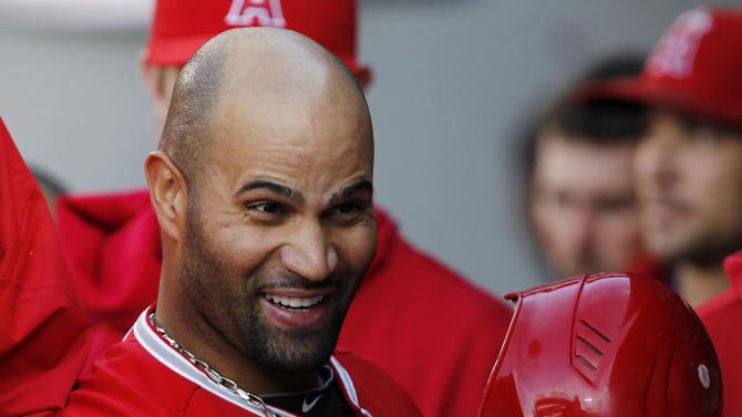 Los Angeles Angels' Albert Pujols smiles in the dugout after his two-run home run against the Seattle Mariners in the first inning in a baseball game Thursday, May 24, 2012, in Seattle. (AP Photo/Elaine Thompson)