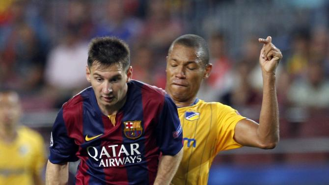 Barcelona's Lionel Messi fights for the ball against Apoel Nicosia's Joao Guilherme during their Champions league soccer match in Barcelona